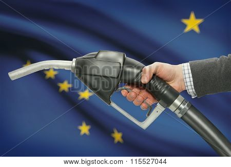 Fuel Pump Nozzle In Hand With Usa States Flags On Background - Alaska