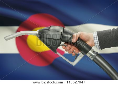 Fuel Pump Nozzle In Hand With Usa States Flags On Background - Colorado