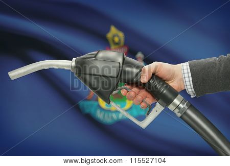 Fuel Pump Nozzle In Hand With Usa States Flags On Background - Maine