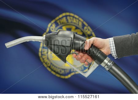 Fuel Pump Nozzle In Hand With Usa States Flags On Background - Nebraska