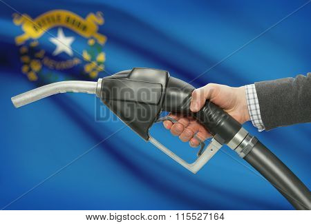 Fuel Pump Nozzle In Hand With Usa States Flags On Background - Nevada