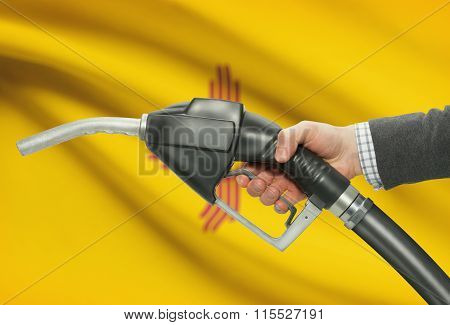 Fuel Pump Nozzle In Hand With Usa States Flags On Background - New Mexico