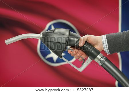 Fuel Pump Nozzle In Hand With Usa States Flags On Background - Tennessee