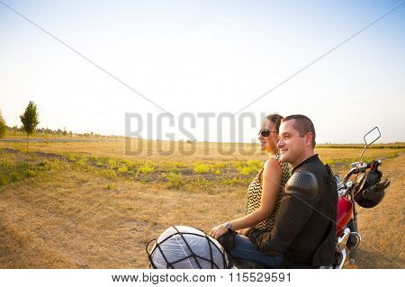 Biker Couple On The Country Road Against The Sky