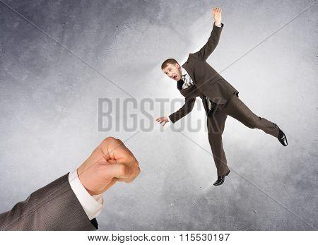 Businessman hitting little man