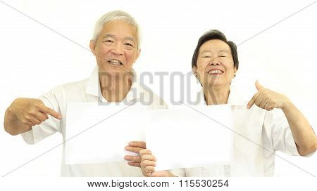 Happy Asian Senior Couple Holding White Blank Sign Ready For Promotion Advertising Banner