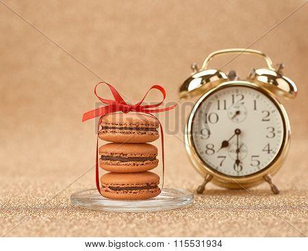 Macarons. Gold stylish alarm clock, breakfast time