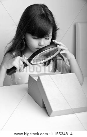 Little girl opening present with magnifier