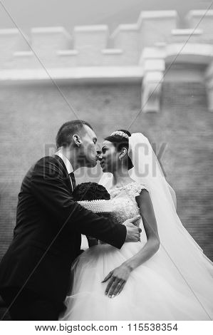 Romantic Newlywed Couple Hugging In Front Of Old Castle Wall Closeup B&w
