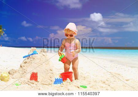 cute little girl building sandcastle on beach