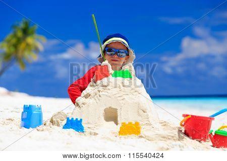 little boy building sandcastle on beach