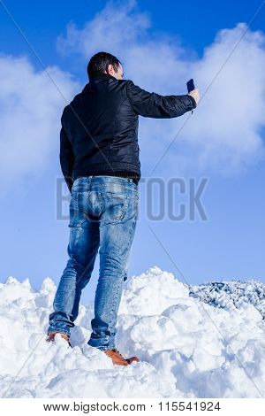 Young Male On Snow Taking Picture With Smartphone