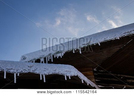 Frozen Wooden Roofs With Icicles And Blue Sky Background