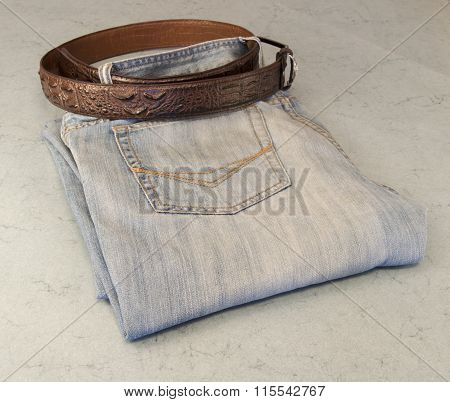 Folded Men's Jeans With Leather Belt On Blue Background