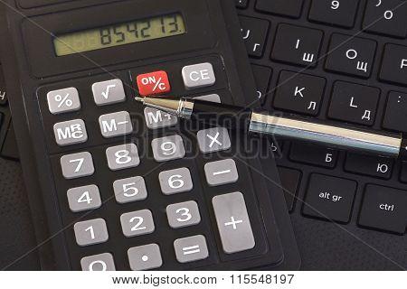 Calculator ,ballpoint pen on the keyboard