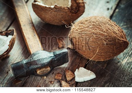 Coconuts And Hammer On Old Wooden Table