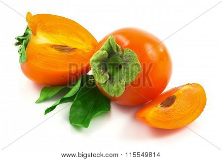 Group Of Ripe Fresh Persimmons With Slices And Bunch Of Green Leaves