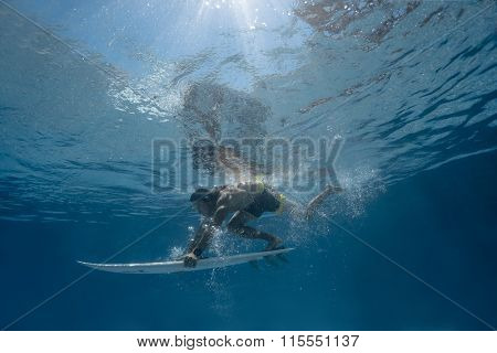 Surfer with surf board dive underwater with fun under big ocean wave