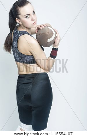 Sport Concepts And Ideas. Professional Female Athlete Posing With American Football Ball.
