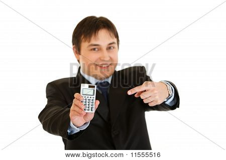 Smiling modern businessman pointing finger on calculator isolated on white