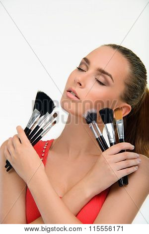 Young woman with a lot of make-up brushes.