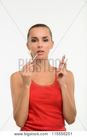 Sensual woman applying gloss on her lips.