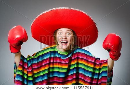 Girl in mexican vivid poncho and box gloves against gray