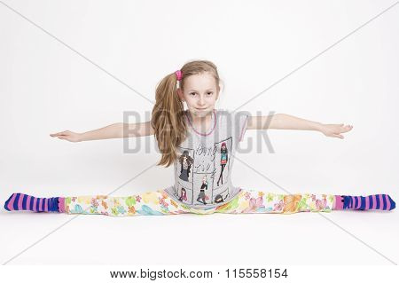 Happy And Cheerful Caucasuan Blond Girl Stretching And Doing The Splits. Positive Facial Expression