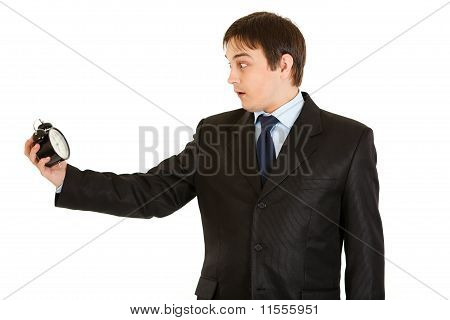 Shocked young businessman holding alarm clock. Lost time concept isolated on white