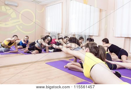 Group Of Seven Caucasian Sportive Women Stretching Indoors On Sport Mats.