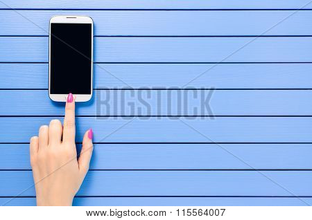 Female hand using mobile phone over blue wooden table