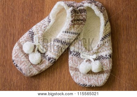 Knitted slippers with pompoms on wood floor.