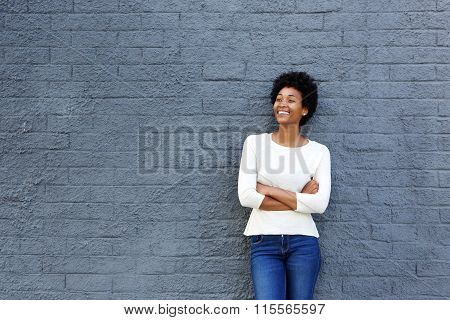 Happy African Woman Standing Against A Gray Wall