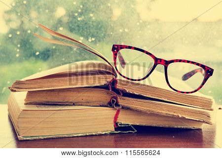Set Of Reading Glasses And Books Over The Window