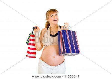 Glücklich pregnant Woman, die holding Einkaufstaschen in Händen, isolated on white