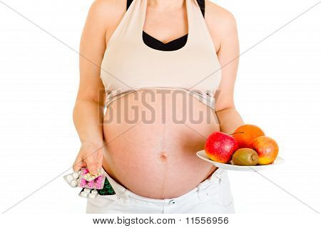 Pregnant woman holding pills and fruits isolated on white. Close-up.