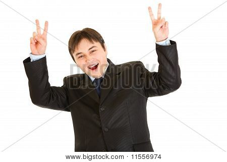 Laughing young businessman showing victory gesture isolated on white
