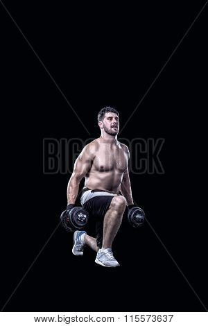 Shirtless sportsman doing knee-bends with dumbbells isolated on black background