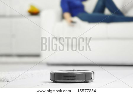 Robotic vacuum cleaner cleaning the room while woman resting on sofa, closeup