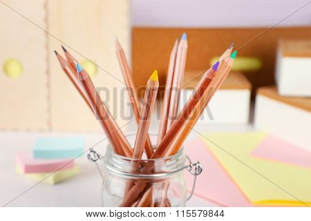 Set of coloured pencils in a glass pot, close up