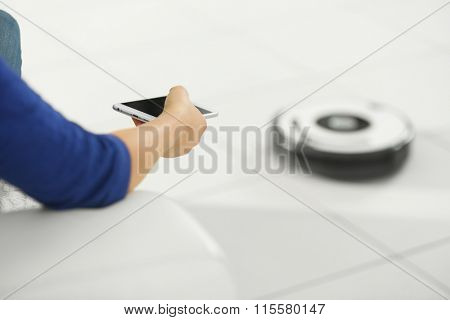 Woman using remote control toward robotic vacuum cleaner in the room