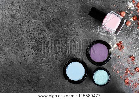 Three shadows with nail polish and crushed rouge on gray background