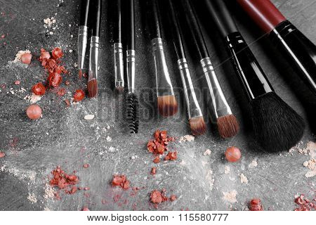 Makeup brushes and crushed rouges on gray background