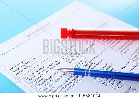 Blood in test tubes, pen and investigation form on the table