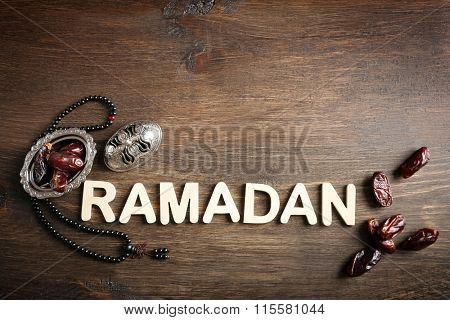 Image of word RAMADAN with rosary and dates fruit on wooden background, close up