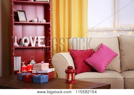 Colourful decorated interior. Comfortable living room, table with gift boxes and candles on it is close up