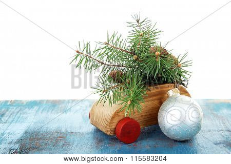 Wooden toy car with fir sprigs and bauble a table over white background