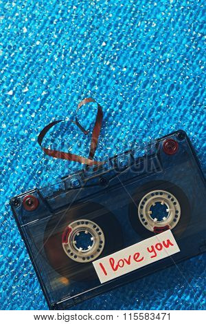 Retro audio cassette with tape in shape of heart on blue textured background