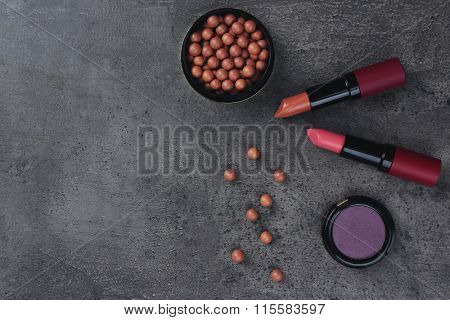 Make-up lipsticks, eye-shadow and blusher, on grey background