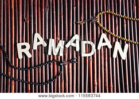 Image of word RAMADAN with rosary on wooden background, close up